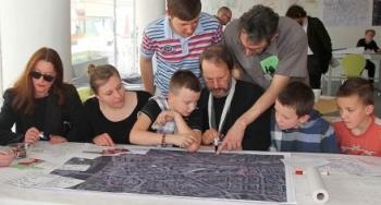 """Stadtplanung ist nun nicht mehr nur Angelegenheit der Stadt und der Bauunternehmen, sondern bezieht alle Einwohner ein. Die Gemeinschaft in der z.B. eine neue Schule gebaut werden soll, wird jetzt teil der Planung. Diese neue Methode, mit der Collaborative Learning in dem Prozess der Stadtplanung angewendet wird, nennt man auch """"Charette""""(Bruffee 1973: 634 - 635)."""